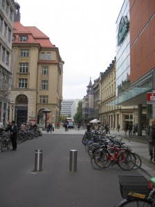 Many bikes, with modern and historic Leipzig buildings in the background