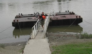 Zach carrying his trike over a narrow ferry ramp