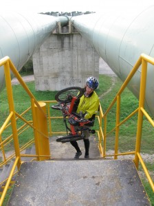Zach carries his trike up the stairs on the pipeline bridge