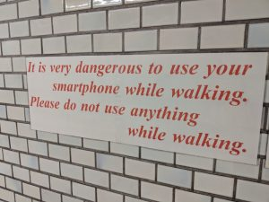 Sign: It is very dangerous to use your smartphone while walking. Please do not use anything while walking.
